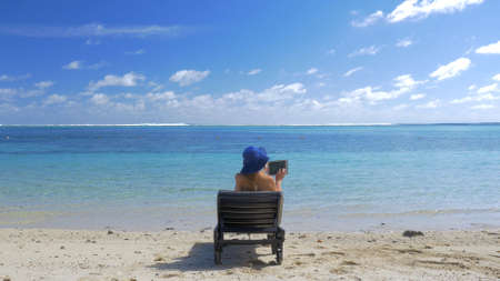 Back shot of a woman in hat with tablet computer relaxing in chaise-longue on blue lagoon beach. Summer vacation in tropics Фото со стока
