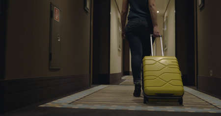 Steadicam and low angle shot of a woman traveler with suitcase in hotel corridor. She is going to check-in or leave the hotel Фото со стока