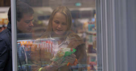 Young couple is standing by the freezer in grocery store and picking packages with frozen food.