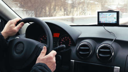 Close-up shot of a man driving a car in winter city. GPS device on the dashboard helps him to find the way