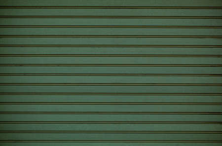 Green wooden wall cladding background texture with repeat pattern of horizontal line in a full frame view. This is a lighter version, a darker version is also available in the portfolio