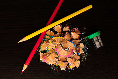 Colored pencils on dark background. Crayons. Color pencils with sharpening and shaves.