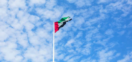 United Arab Emirates flag flying against beautiful blue sky with clouds. UAE celebrates it's national day on 2nd December every year.