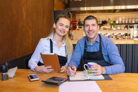 Happy man and woman going through paperwork together in their restaurant. Small family restaurant owners discussing finance calculating bills and expenses of their small business. 版權商用圖片