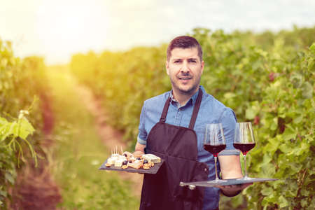Modern wine maker in vineyard holding samples of red wine and different selection of cheese and salami – wine tasting with smiling man sommelier wearing apron serving bio farm products at winery