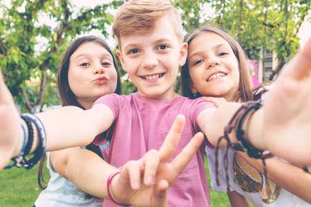 Happy best friends kids taking selfie outdoors in garden party