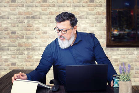Stressed mixed race businessman at desk working late in office
