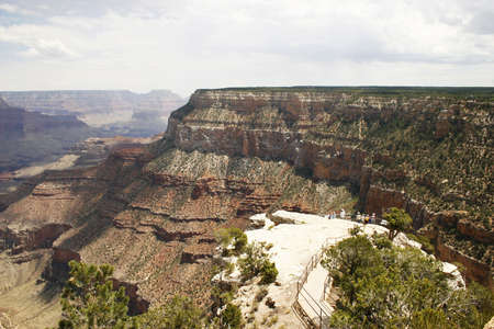 A view of the Grand Canyon south rim looking east with visitors in the foreground.