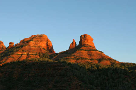 bight: The mountains in Sedona AZ are bight red at sunset. Stock Photo