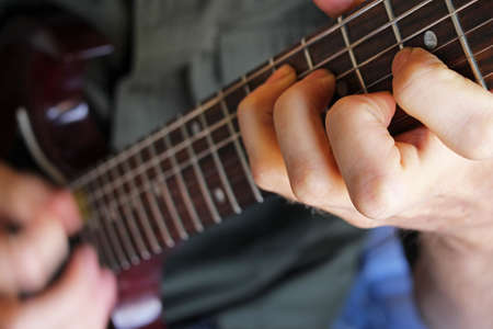 chord: Closeup on musicians hand forming a chord on an electric guitar.