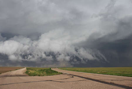 Powerful thunderstorm winds gust outward, stirring up dust on the prairie