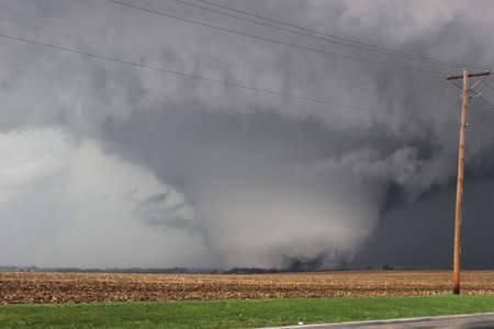 A massive, destructive tornado scours the farmland in Illinois. Imagens