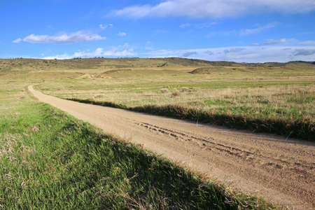 Long straight gravel road in the prairie. 版權商用圖片