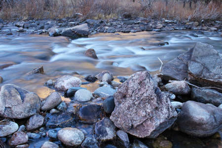 Icy cold water flows over the rounded rocks of the Poudre River in Colorado Stock Photo