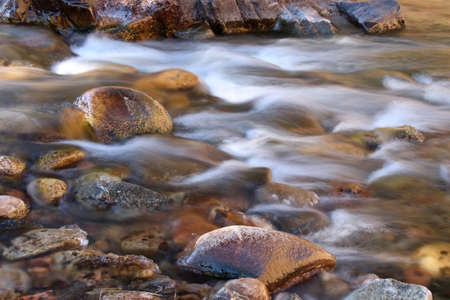 poudre river: Icy cold water flows over the rounded rocks of the Poudre River in Colorado Stock Photo