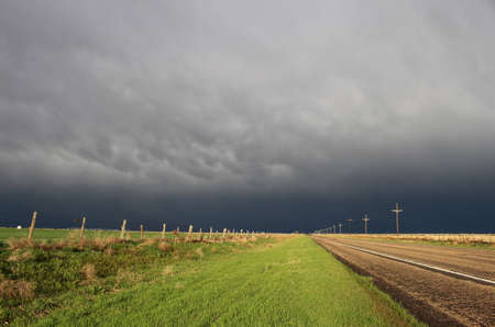 great plains: The sun shines brightly along a lonely highway while a dark and stormy sky looms on the horizon. Stock Photo