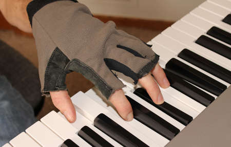 chord: A pianist wearing fingerless gloves strikes a chord on the piano. Stock Photo