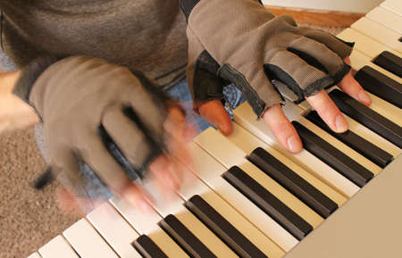 ivories: A pianist fights the chill of winter by playing with fingerless gloves. One hand strikes a chord while the other plays rapidly.