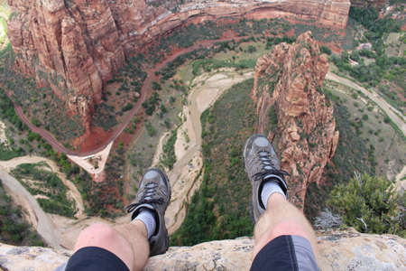 First person perspective shot from a hiker sitting at the edge of a cliff at Angels Landing in Zion National Park.