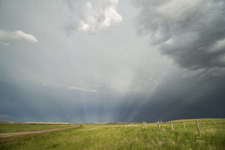 Sun rays radiate through the mist behind a passing storm on the prairie. 版權商用圖片