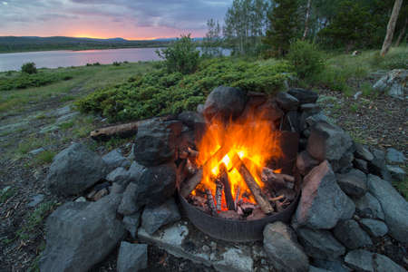 A campfire burns hot at a lakeshore campsite, as the sun sets in the mountains of Wyoming.