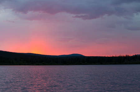 A beautiful pink glowing sunset over a mountain lake. Stock Photo