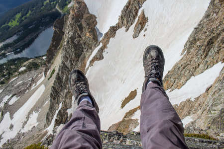 A hiker dangles his legs over the edge of a cliff in the Rocky Mountains.
