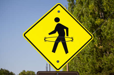 vandalism: A bright yellow pedestrian crosswalk sign with a hula hoop drawn onto it.
