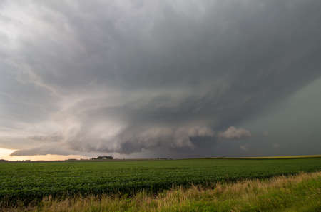 A supercell thunderstorm fills the sky over farmland in the American Midwest.