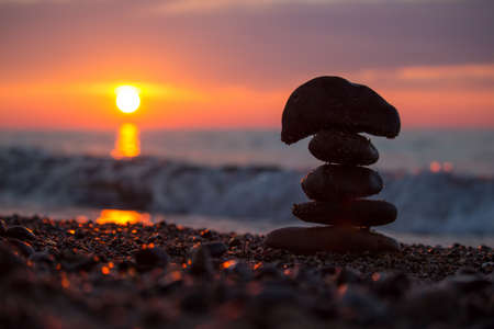 A rock cairn stacked on the beach of Lake Superior at sunset. Stock Photo