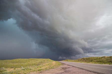 A dangerous thunderstorm rapidly approaches a rural highway in Nebraska.