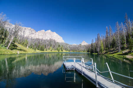 A pristine alpine lake in Wyoming with a small pier.