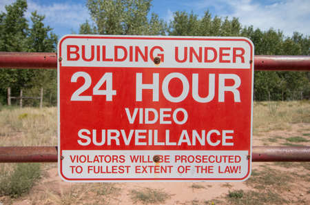A red and white sign warns of video surveillance.