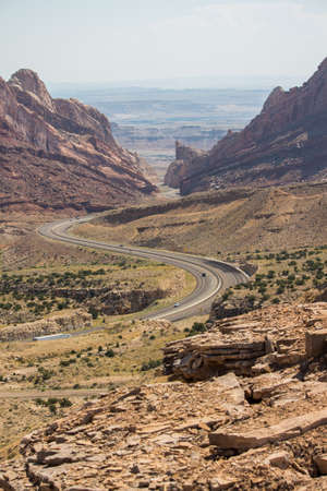 A desert highway winds through steep rock walls.