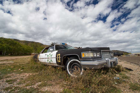 A broken down police car rests in an overgrown gravel lot. Stock Photo