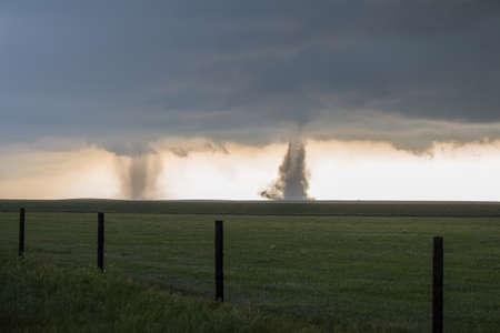 Twin tornadoes churn the dirt on the high plains of Colorado.