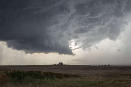 A rope tornado funnel dissipates underneath the updraft of a supercell thunderstorm.