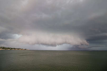 A supercell thunderstorm and wall cloud looms over a lake.