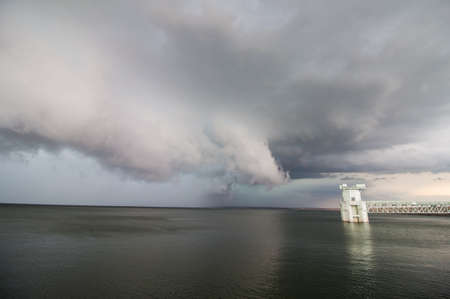 A supercell thunderstorm and shelf cloud loom over a lake. All boats have left the water because of the storm.