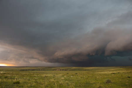 A severe thunderstorm approaches over the great plains landscape. The early evening sun casts an eerie light.