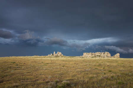 A dark and stormy sky behind a rocky ridge on the prairie.