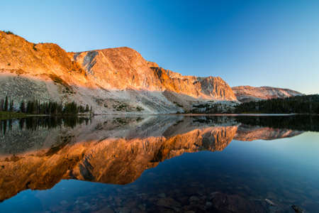 Morning sunlight illuminates the mountains and reflects off the calm waters of an alpine lake.
