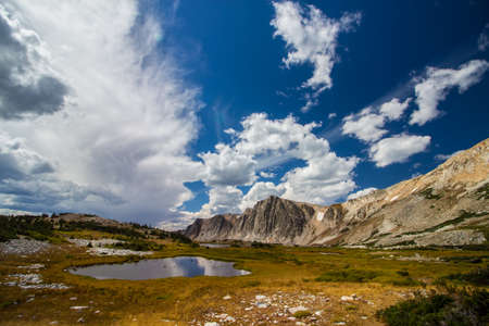 A beautiful landscape of mountains and lakes on a partly cloudy day in late summer.
