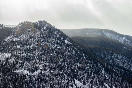 Light snow falls in the Rocky Mountains as sunshine peeks through the clouds. Stock Photo