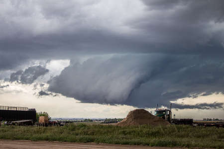 A large gray wall cloud develops with a supercell thunderstorm over the high plains.