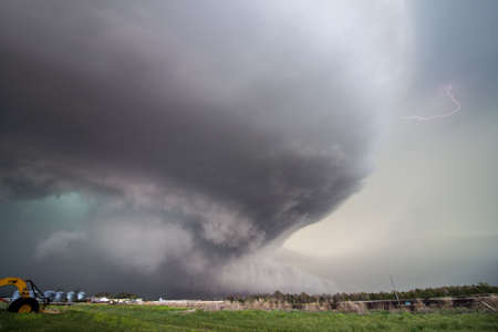 A huge supercell storm with a ground scraping wall cloud and lightning bolt fills the sky.