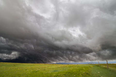 Turbulent dark storm clouds roll over the a field of green grass creating a beautiful cloudscape.