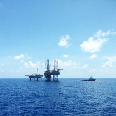 oil platform: An oil platform with a supply vessel nearby doing cargo operation
