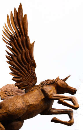 Chainsaw sculpture of a wooden Pegasus unicorn taking flight isolated on white photo