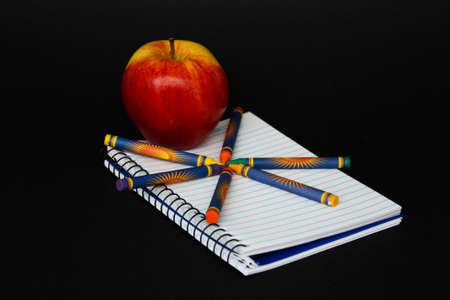 An Apple on a notebook with crayons isolated on black  photo